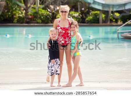 Cute Family at a large outdoor swimming pool - stock photo