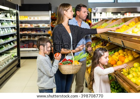 Cute family choosing groceries together at the supermarket - stock photo