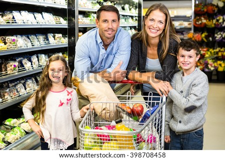 Cute family doing grocery shopping together at the supermarket - stock photo