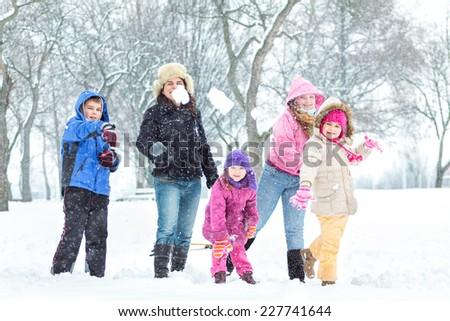 Cute family having fun in the snow  - stock photo