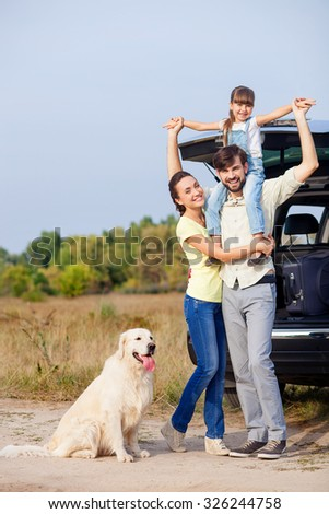 Cute family is resting in the nature and smiling. They are standing near car and dog. The father is holding daughter on shoulders. His wife is embracing him with love - stock photo
