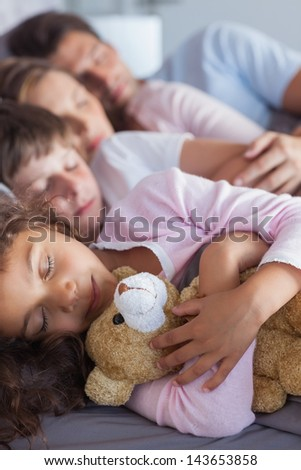 Cute family napping together in bed - stock photo