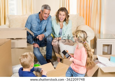 Cute family opening boxes in living room - stock photo