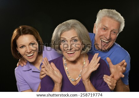 Cute family portrait , adult daughter with senior parents surprised