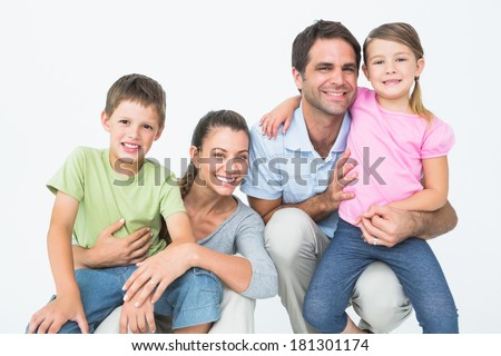 Cute family posing and smiling at camera together on white background - stock photo