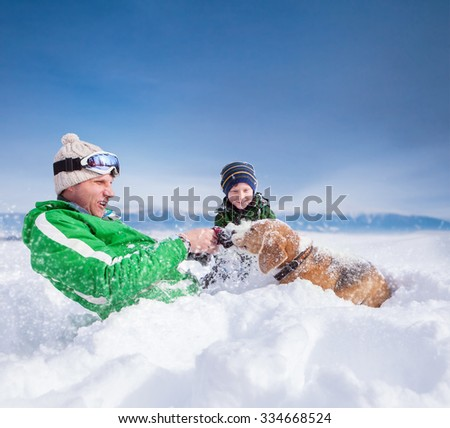 Cute family scene: father and son play with dog during mountain walk - stock photo