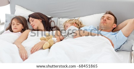 Cute family sleeping together in the parents's bed - stock photo