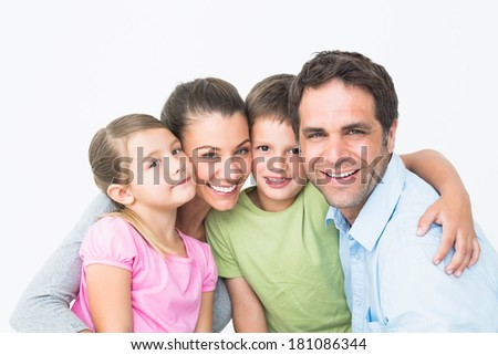 Cute family smiling at camera together on white background - stock photo