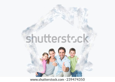 Cute family smiling at camera together showing thumbs up against house outline in clouds - stock photo