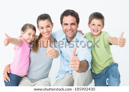 Cute family smiling at camera together showing thumbs up on white background - stock photo