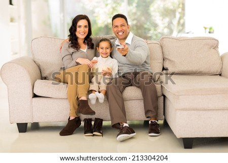 cute family watching movie together at home - stock photo