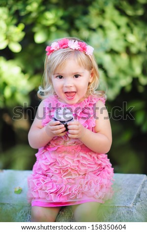cute fashion little girl eat happy birthday pink cupcake - stock photo