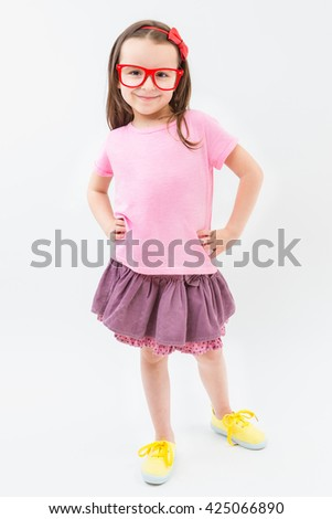 Cute fashion-monger girl in pink dress tshirt and skirt red glasses frames. Trendy kid with empty no image tshirt you can place your own text information or ad logo. Studio shot. White background