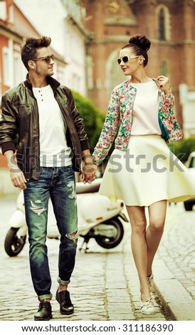 Cute fashionable couple on city street - stock photo