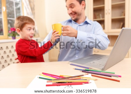 Cute father and son are sitting at the table at home and using a laptop. The man is giving a cup of tea to the boy. The kid is refusing to drink it and drawing faces. The man is smiling - stock photo