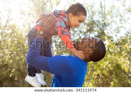 Cute father and son playing together at the park - stock photo