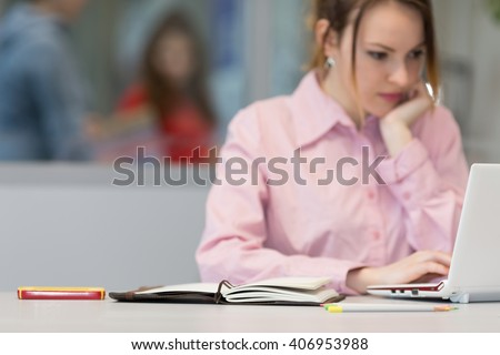 Cute female Businessperson thinking and looking into Computer Telephone Pencils and Workbook on Foreground - Focus on Workbook edge - stock photo