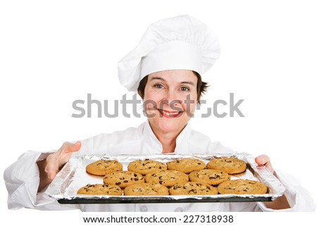 Cute female chef in her uniform, holding up a tray of delicious, freshly baked chocolate chip cookies.  Isolated on white background.