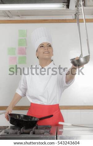 Cute female chef working in hotel industrial kitchen preparing food for the restaurant