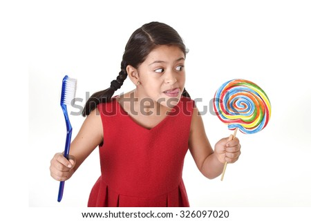 cute female child holding big spiral lollipop candy and huge toothbrush in dental care and health concept and unhealthy sugar abuse isolated on white background - stock photo