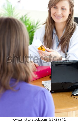 Cute female doctor holding medicine in her office - stock photo