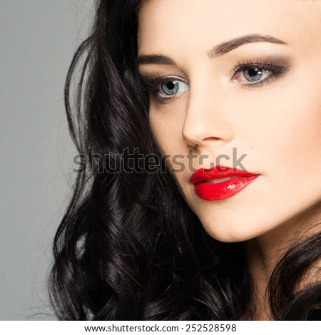 Cute female face with stage makeup smokey eyes and red lips - stock photo