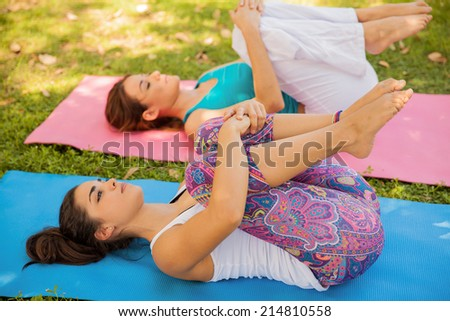 Cute female friends doing some stretching and getting ready for their yoga practice - stock photo