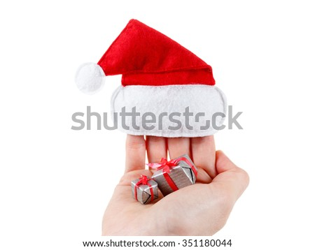 Cute female hand holding a santa hat and christmas gifts. Isolated on white background - stock photo