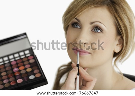 Cute female having her make up done by a make up artist in a studio