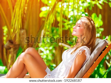 Cute female on tropical resort, sitting on deckchair with closed eyes and taking sun bath, enjoying exotic nature, summer vacation on Maldives