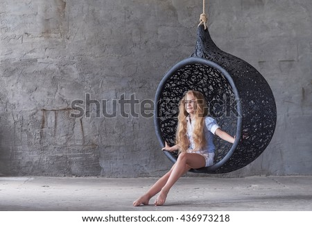 Cute female posing in swinging oval chair over grey background. - stock photo