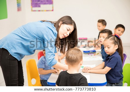 Cute female preschool teacher patiently explaining his work assigment to one of her students in a classroom
