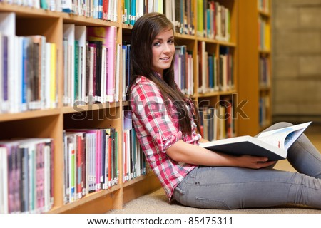 Cute female student holding a book in a library