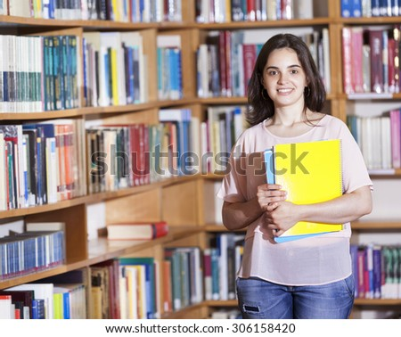 Cute female student holding notebooks at the university library