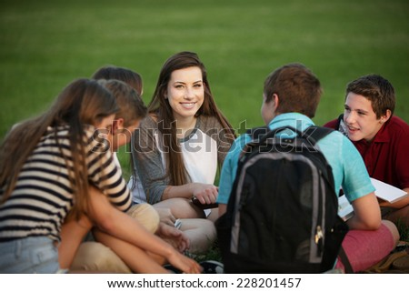 Cute female teen student studying with friends outdoors