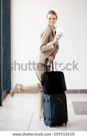 cute female traveller holding south african cash note - stock photo