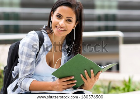 cute female university student listening music on campus - stock photo