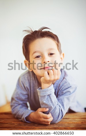 Cute five year old European boy posing over white studio background. Child with surprised smile and funny hairstyle. - stock photo