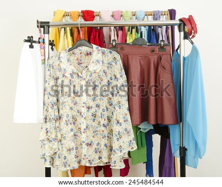 Cute floral outfits displayed on a rack. Wardrobe with colorful summer clothes and accessories. - stock photo