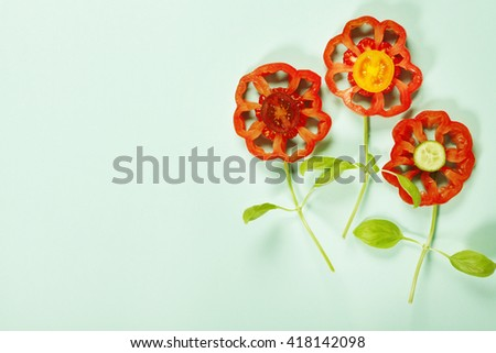 Cute flowers made of fresh organic vegetables on blue background - Cooking, Gardening, Raw Food, Vegetarian or Clean Eating concept - stock photo