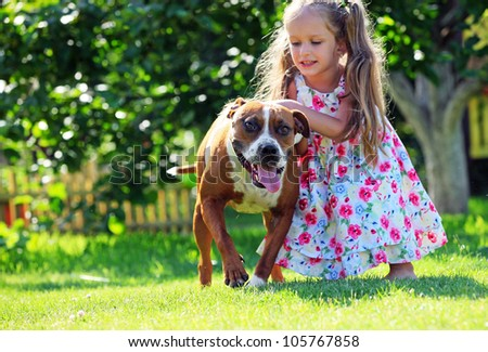 Cute four-year old girl playing with her Staffordshire terrier dog in front yard - stock photo