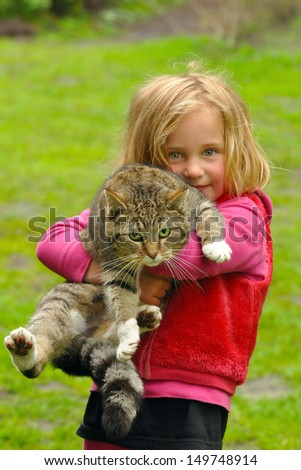 Cute four year old girl with her cat - stock photo