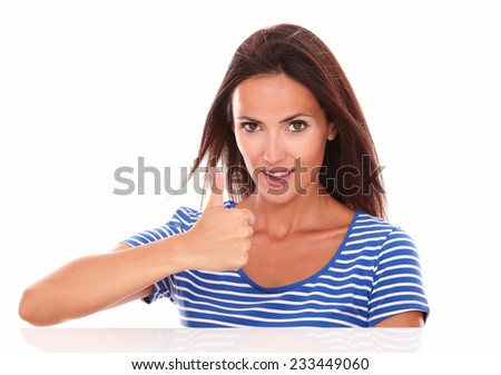 Cute friendly girl with thumbs up gesturing an ok sign in white background