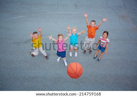 Cute friends playing basketball on sports ground - stock photo