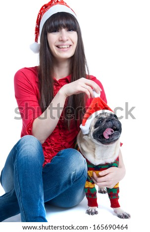 Cute friends pretty girl and pug dog pet wearing red Santa Claus caps, having fun, smiling, girl holding a dog pompon, dog showing tongue, looking at camera. Isolated on white, main focus on dog - stock photo
