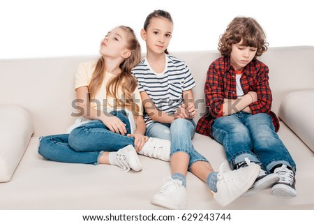 Cute friends sitting on couch and do not talking with each other