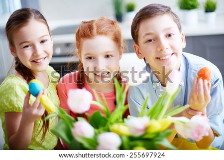 Cute friends with painted Easter eggs - stock photo