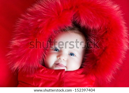 Cute funny baby girl with big blue eyes in a warm winter jacket with a red hood - stock photo