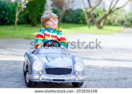 Cute funny boy driving big toy old vintage car and having fun, outdoors. Active leisure with kids outdoors  on warm spring or autumn day. - stock photo