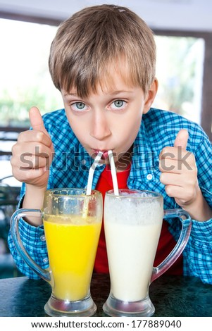 Cute funny child drinking fruit cocktails from two big glasses with straws. Creative drink concept.  - stock photo